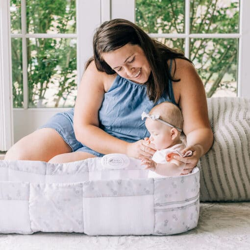 Mom sitting up on the rug in home with baby sitting up in snuggle nest infant lounger