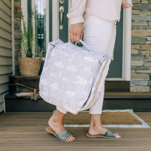 woman's feet and arm holding closed snuggle nest and walking up to home on deck