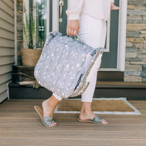 Mom carrying snuggle nest trees lounger while walking across front porch