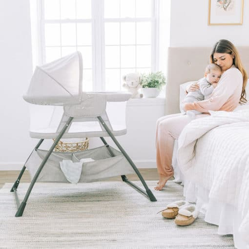 Mom sitting on side of bed holding baby with bassinet next to them.