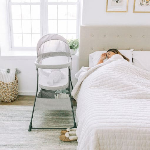 Mom laying in bed next her a baby bassinet with canopy