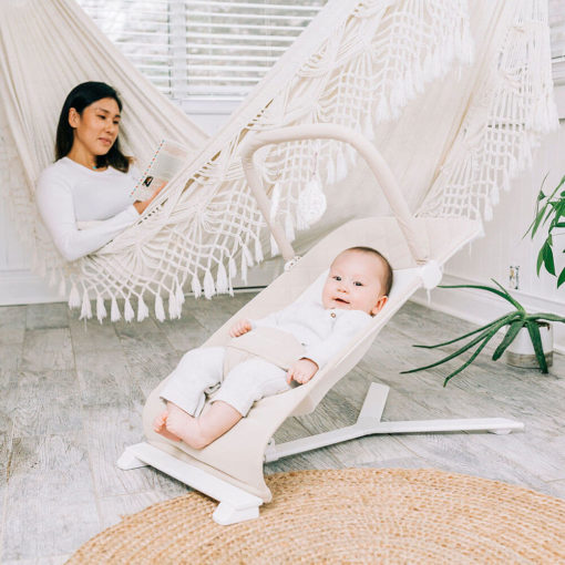 Mom sitting in hammock while baby sits in the Organic Oat bouncer