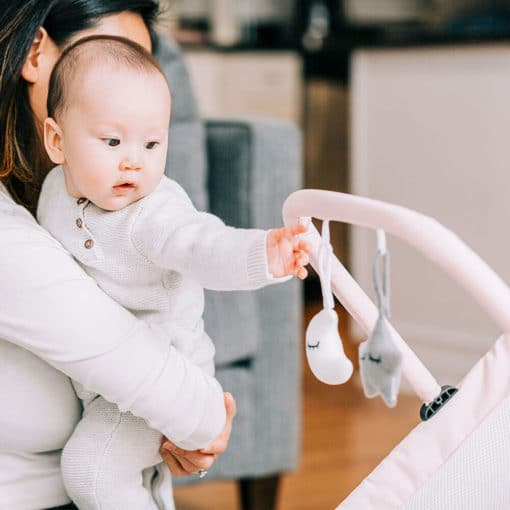 mom holding baby and baby is playing with the toy hanging off pink bouncer chair