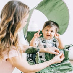 Mom hooking baby into moss colored go with me portable chair