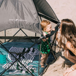 Baby playing in the eclipse playard on the beach with her mom smiling at her