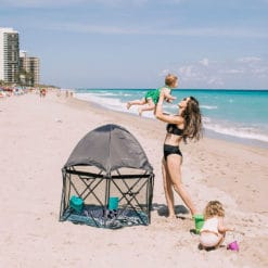 Mom holding baby in the air on the beach with the eclipse playard next to them