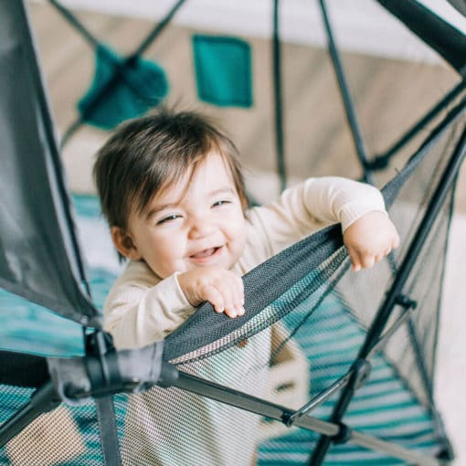 Baby standing in the eclipse playard in a bedroom smiling up at camera