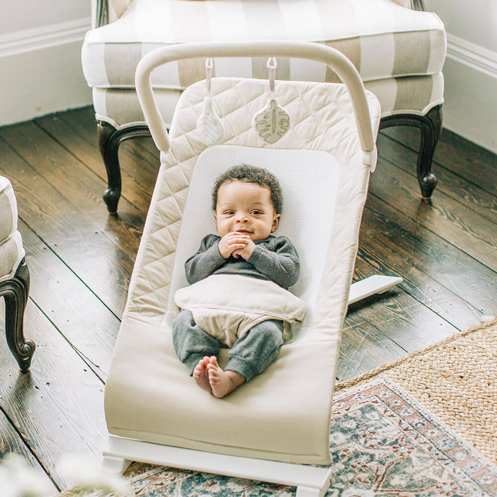 baby sitting in baby bouncer with hand folded smiling