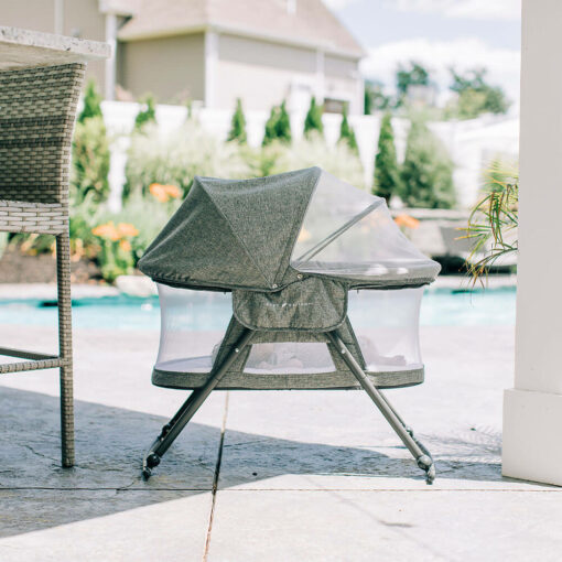 slumber bassinet with baby inside in front of pool outside