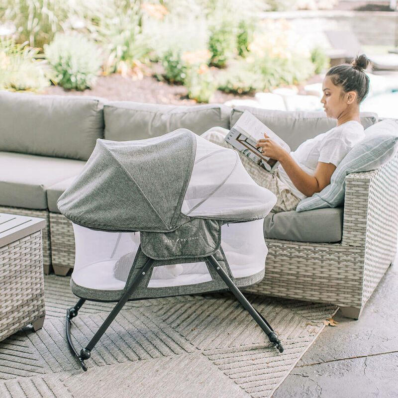 mom sitting outside on patio couch with baby inside bassinet