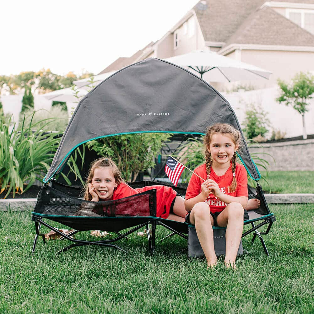 two little girls in red shirts sitting on travel cot in backyard
