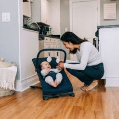 baby sitting in indigo blue baby bouncer chair on hardwood floor with mom leaning down over talking to baby