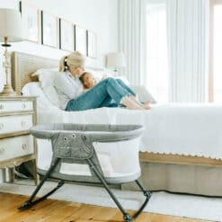 mom sitting on bed with daughter with baby next to them in slumber bassinet