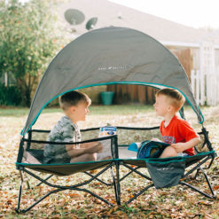 two children sitting in their bungalow cot on the lawn