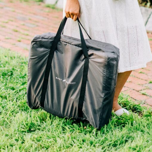 woman carrying bassinet that is inside the grey carry bag