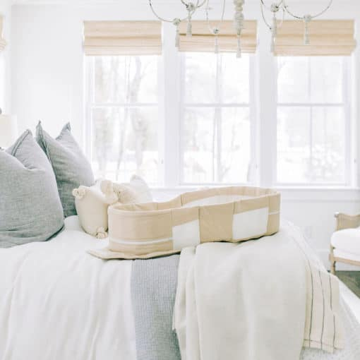 organic snuggle nest opened up on top of a bed in a bright beautiful bedroom