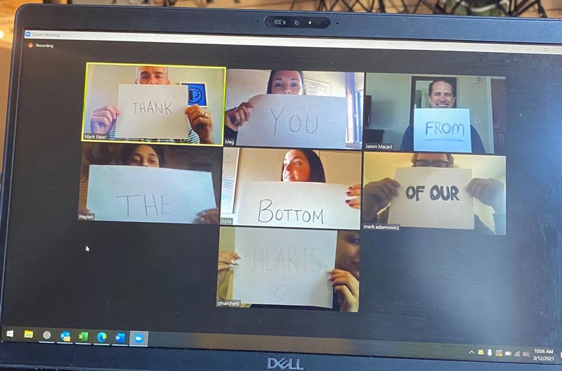 a computer screen with 7 coworkers holding up signs to thank customers on a zoom call