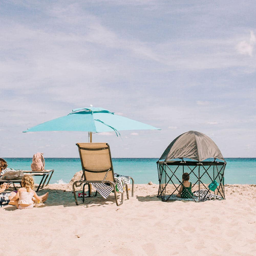Playard facing the water with baby inside on the beach with little sister and chair and beach umbrella