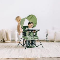 baby sitting in the moss colored go with me chair in bedroom with sister behind him playing