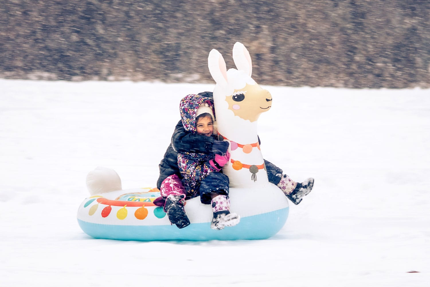 Little girl outside on a snowy day on her llama snow tube having fun.