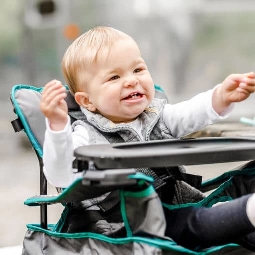 little boy sitting outside in the uplift portable highchair smiling with his hands out