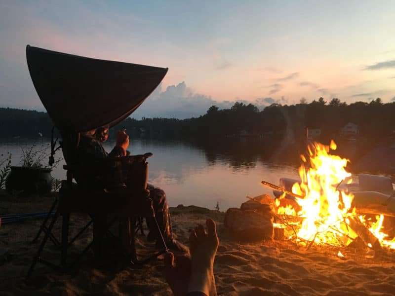 kids camp chair outside in front of the fire by a pond with parents feet