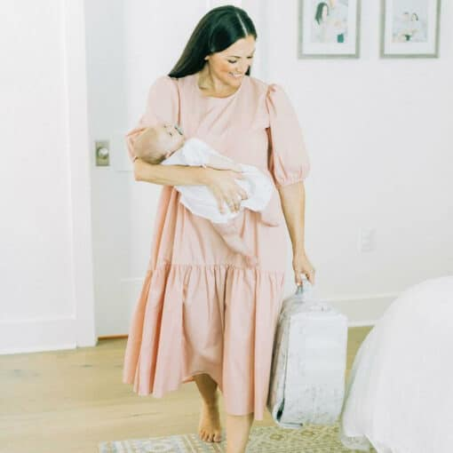 mom in pink dress carrying a snuggle nest lounger