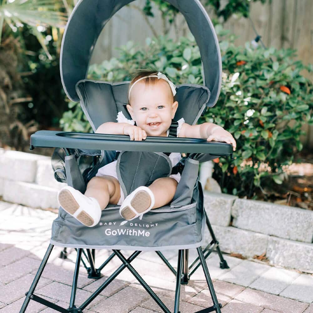 little girl sitting in grey portable chair outside on the patio smiling at camera