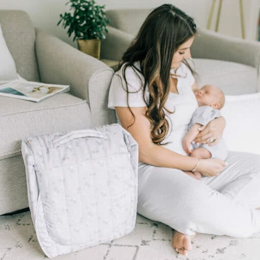 mom sitting on rug holding baby next to floral snuggle nest lounger