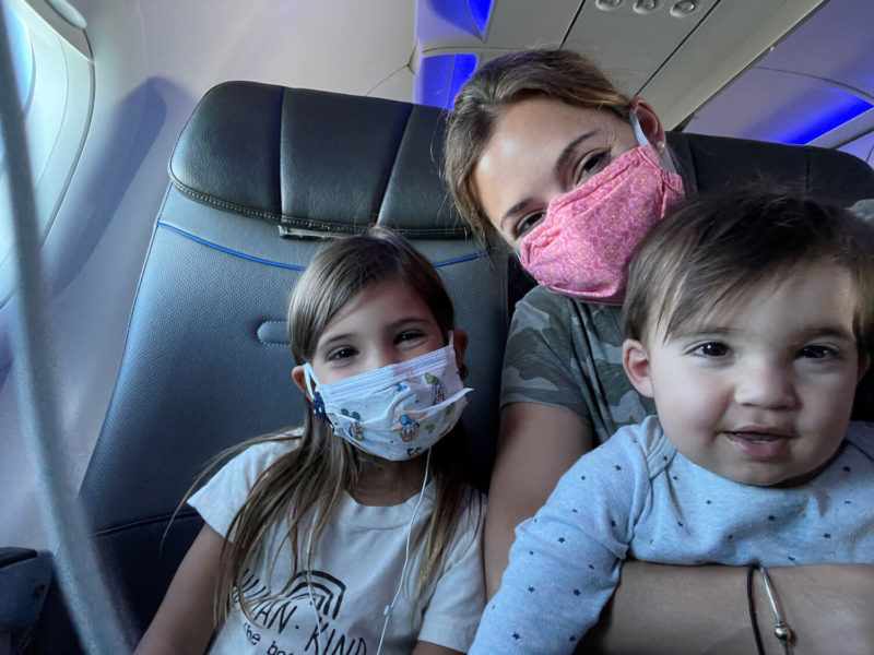 Mom sitting on airplane with her daughter in her daughters by her side and masks on.