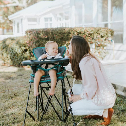 mom talking to baby sitting in his uplift portable highchair outside on the lawn