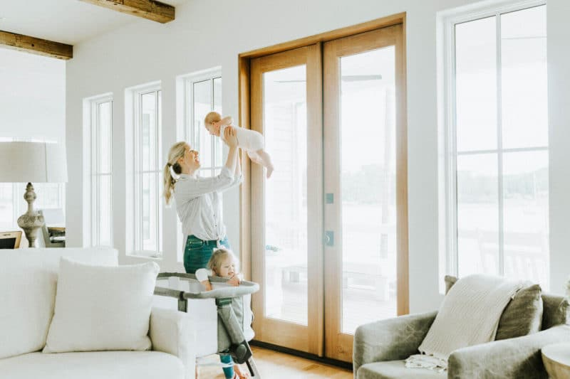 A mother happily holding her baby in the air with her young daughter standing next to her legs.