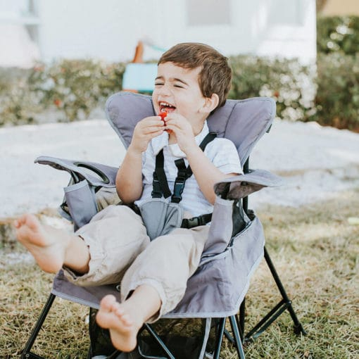little boy laughing in his gray venture chair outside in the yard